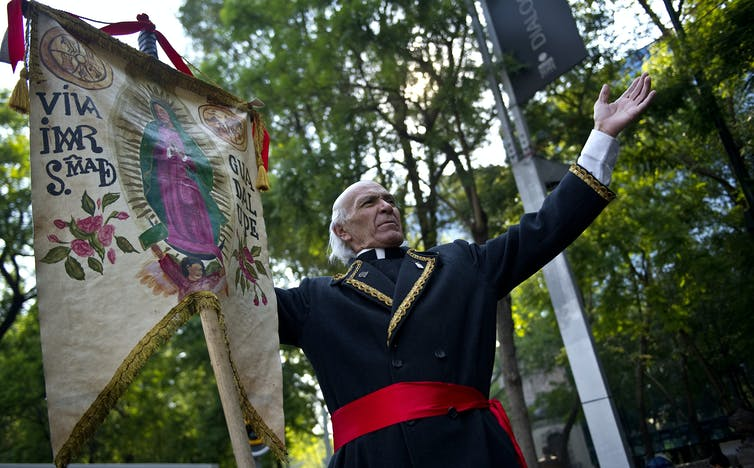 A man dressed as Miguel Hidalgo performs with an image of the Virgin of Guadalupe at the beginning of the 'Relief for Peace with Justice and Dignity' caravan in Mexico City on June 4, 2011.