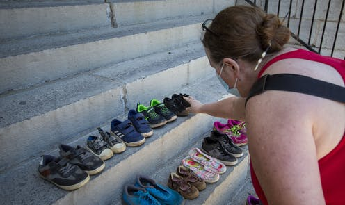 A person touches children's shoes on concrete steps.