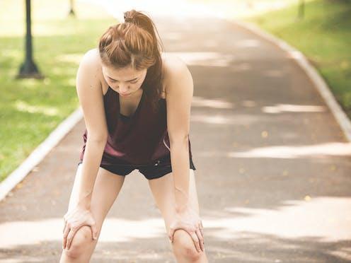 Femme épuisée après une séance d'entraînement en courant dehors à la chaleur