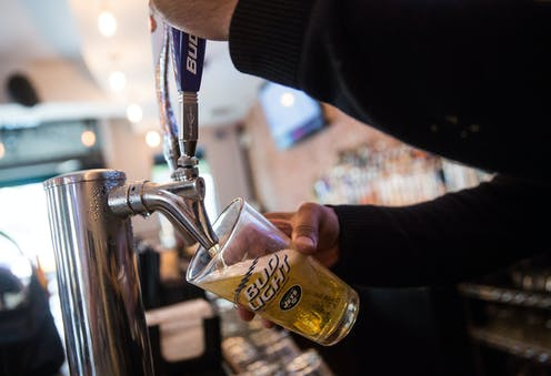 A bartender pours a beer into a Bud Light glass
