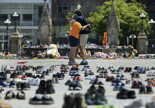 People hug in front of 215 shoes to represent the Indigenous children's remains that were found