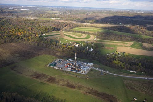 Fracking operation on a concrete slab surrounded by hills and farm fields.