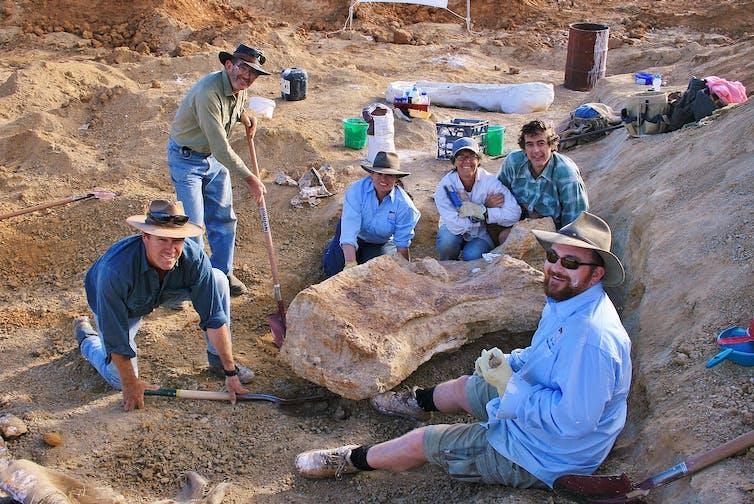 Scientists in hats sitting around a refrigerator-sized bone fragment.