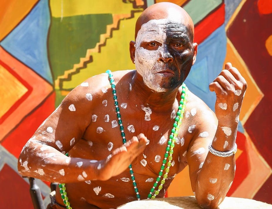 A bright traditional-patterned backdrop with a bald man in front of it beating a drum with one hand. He wears face paint - half his face white, the other black, with white paint spots covering his torso.