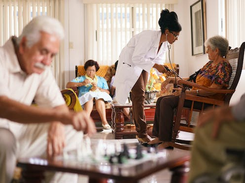 Older adults sitting in a room including a woman knitting, a man playing chess and a woman having her blood pressure checked