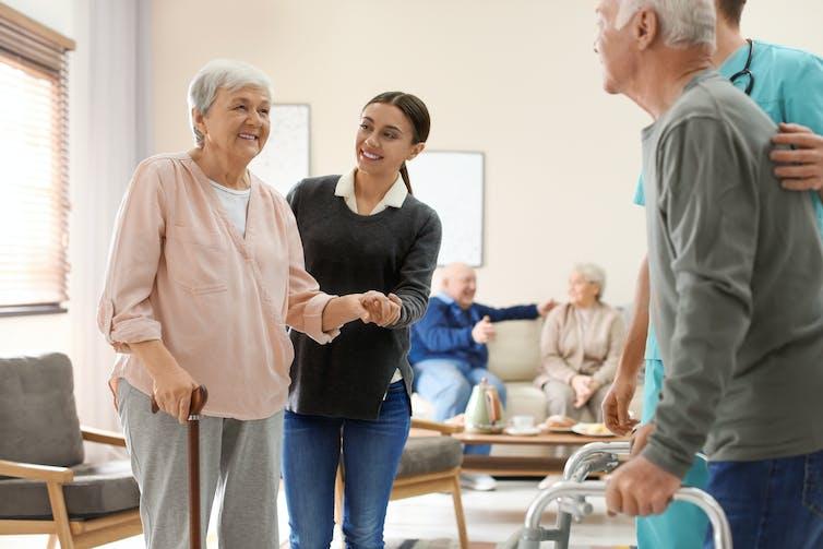 Care staff helping elderly people walk