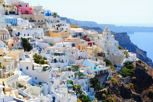 White-walled buildings cover a sunny hillside