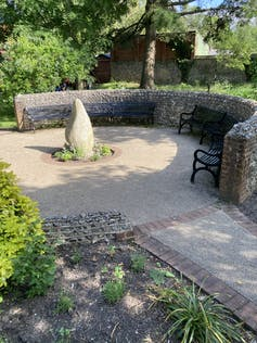 Black benches arranged against a low, semi-circular stone wall in a Chichester park