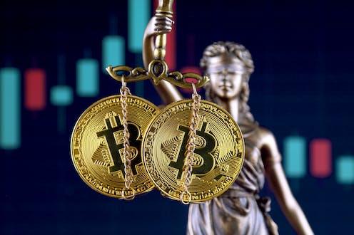 Imagen de la justicia con bitocoines en la balanza.