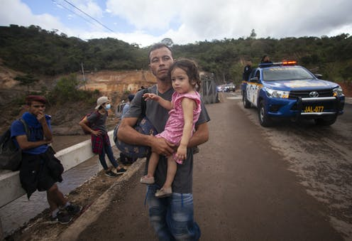 A man carries a young girl while people with backpacks sit beside a road and a police car is nearby
