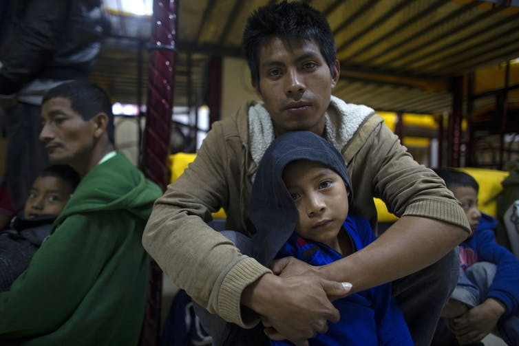 Miguel Martin sits with his 7-year-old son at a migrant shelter in Mexico with other people sitting around them.