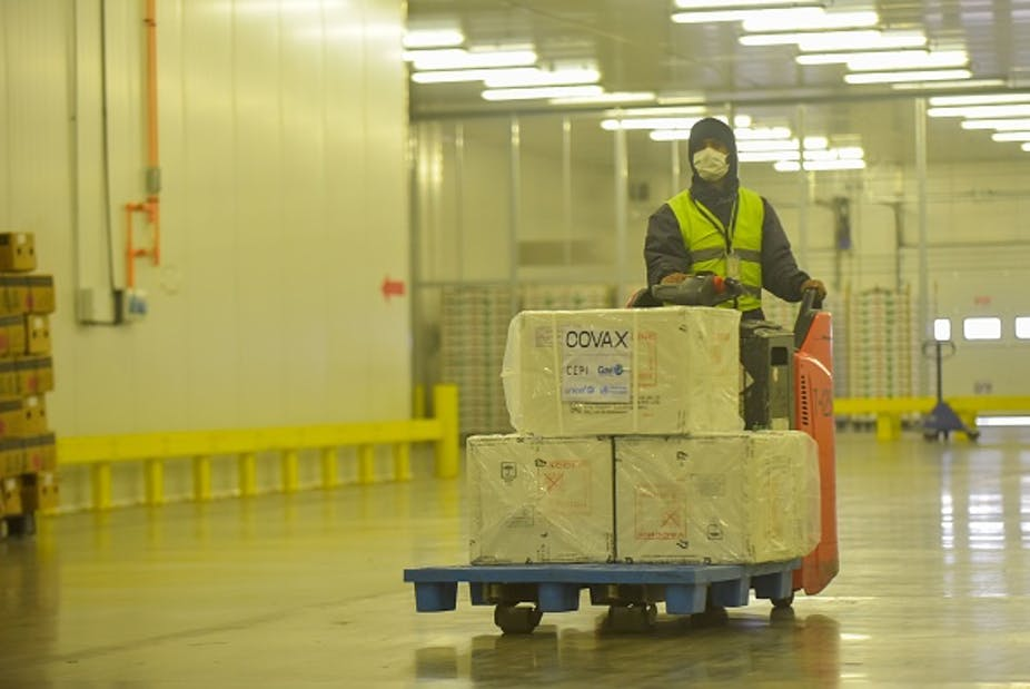 Person wearing protective clothing and face mask sits on a motorised trolley loaded with packages marked COVAX