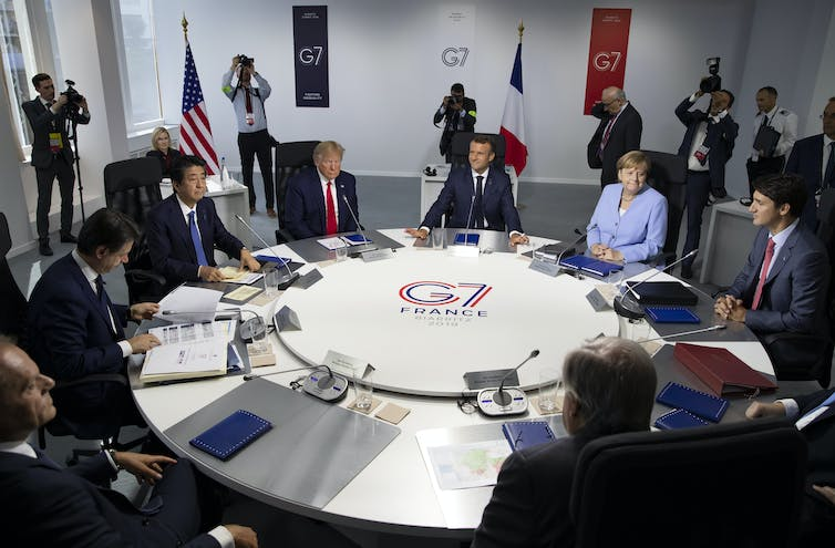 G7 leaders sit around a circular table at the 2019 summit in Biarritz. Visible leaders are Shinzo Abe, Donald Trump, Emmanuel Macron, Angela Merkel, and Justin Trudeau.