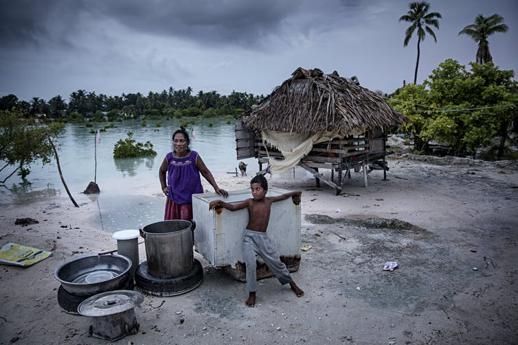 A woman and boy stand outside a home on stilts with cooking pots on the beach where water has risen.