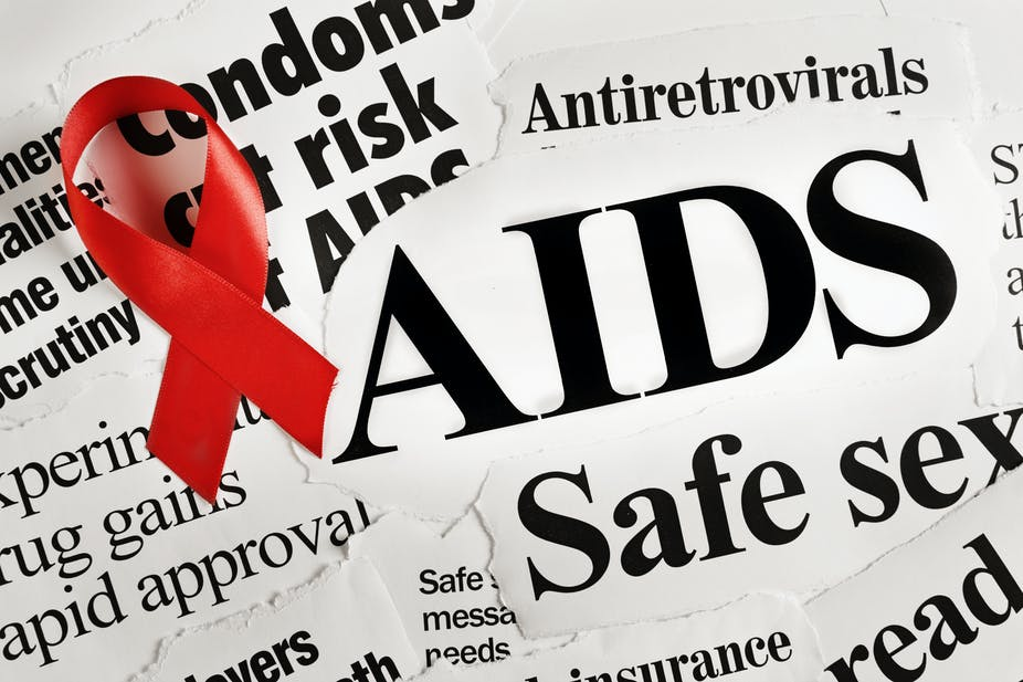 Red AIDS ribbon on headlines concerning the disease