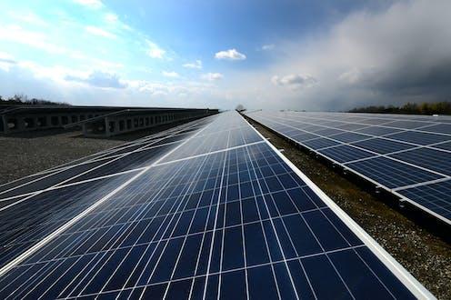 Dark solar panels lie under a blue cloudy sky