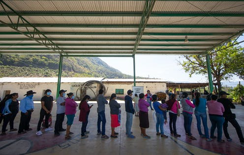 People stand in a line wearing face masks, under a shelter, with mountains in the background
