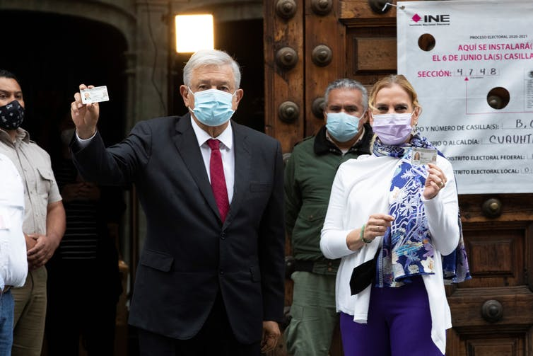 López Obrador holds up a piece of paper, wearing a face mask