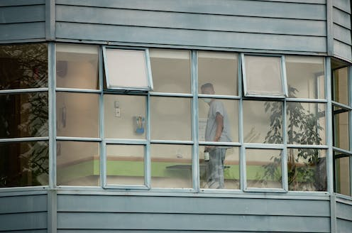 A worker is seen through a window cleaning surfaces.