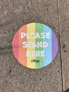 'Please stand here' social distancing sticker in Pride colors