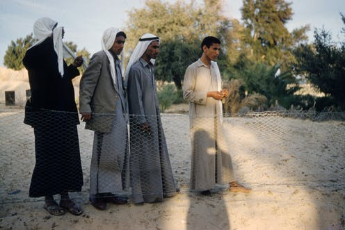Four standing men in grey and beige robes