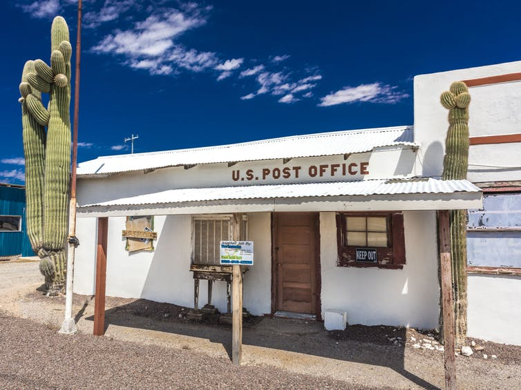 A small white post office that seems to be boarded up; a cactus is in front of it