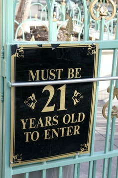 A sign  on a fence saying 'Must be 21 years old to enter.'