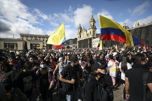 Protesters waving the Colombian flag gather in a protest.