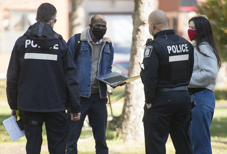 A man holding a laptop and a woman, both wearing masks, talk with two police officers.