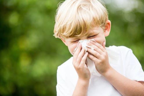 Child sneezing into tissue.