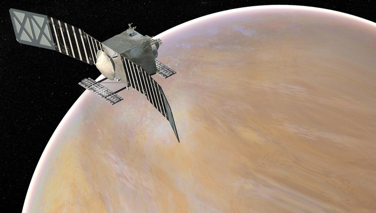 A square satellite with two long solar panels above a tan–colored Venus.