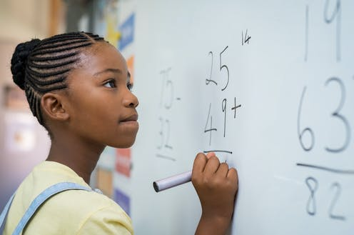 Girls writing maths problems on whiteboard.
