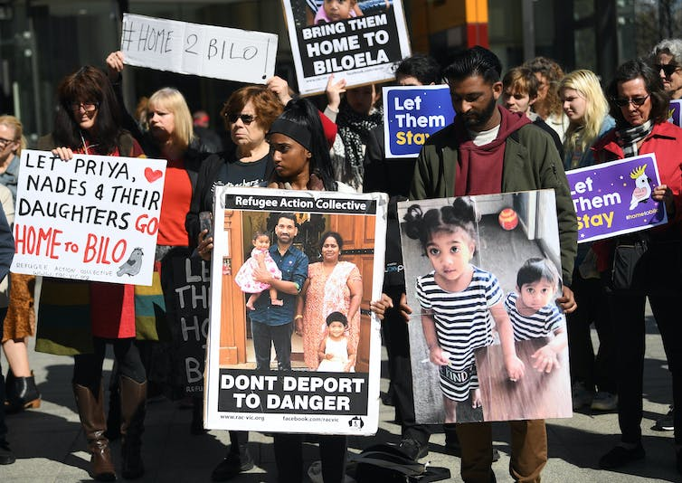 Protesters hold signs in support of the Biloela Tamil family.