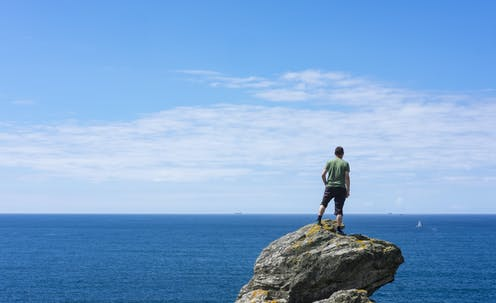 Seorang pria berdiri di atas bebatuan di lautan.