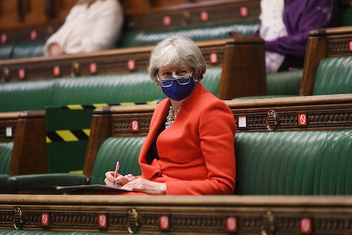 Former prime minister Theresa May sitting on the green benches of the House of Commons wearing a COVID facemask with her glasses pull down over it.