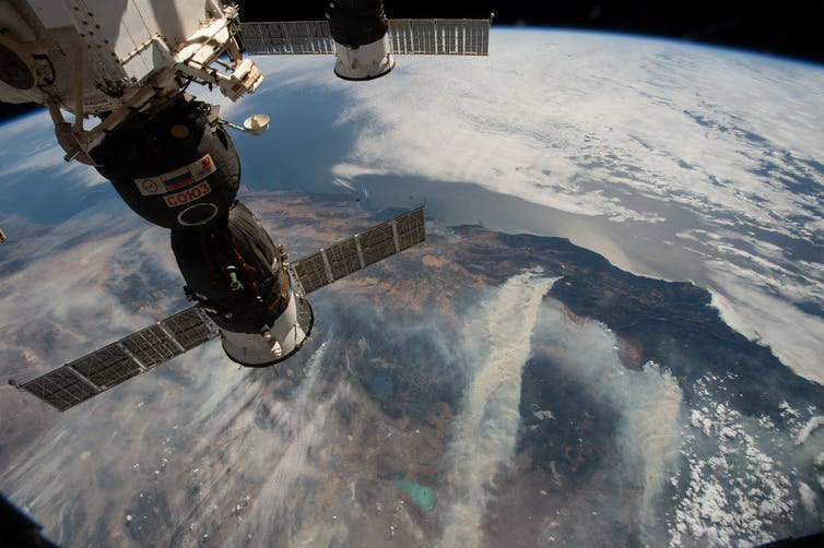 An image shot from the space station showing part of the space station and land below with smoke from wildfires.