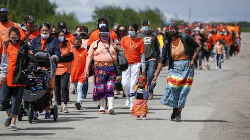 Large group of people wearing orange walk down the road