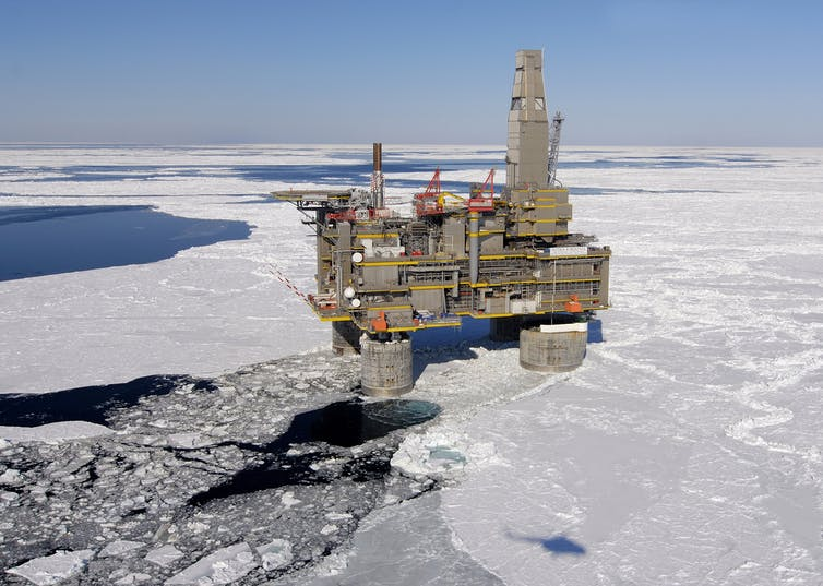 An oil and gas platform stands in icy waters
