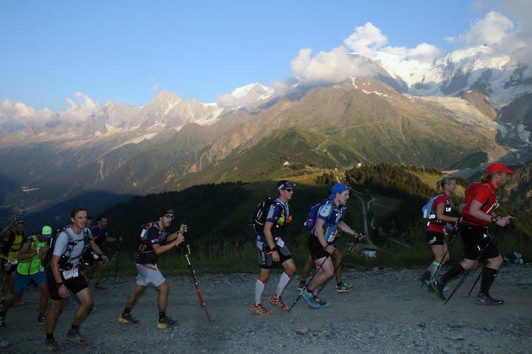 Plusieurs concurrents courent avec des bâtons de marche sur une colline dans les Alpes françaises