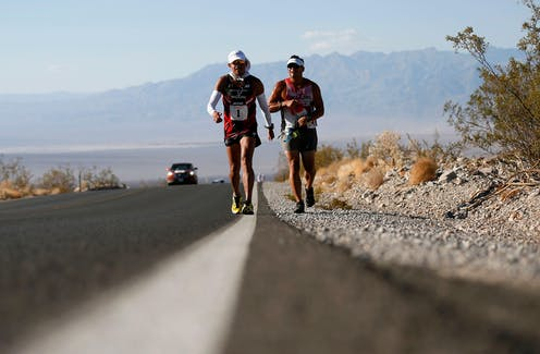Two ultra-marathoners struggle in the heat on a road in the desert