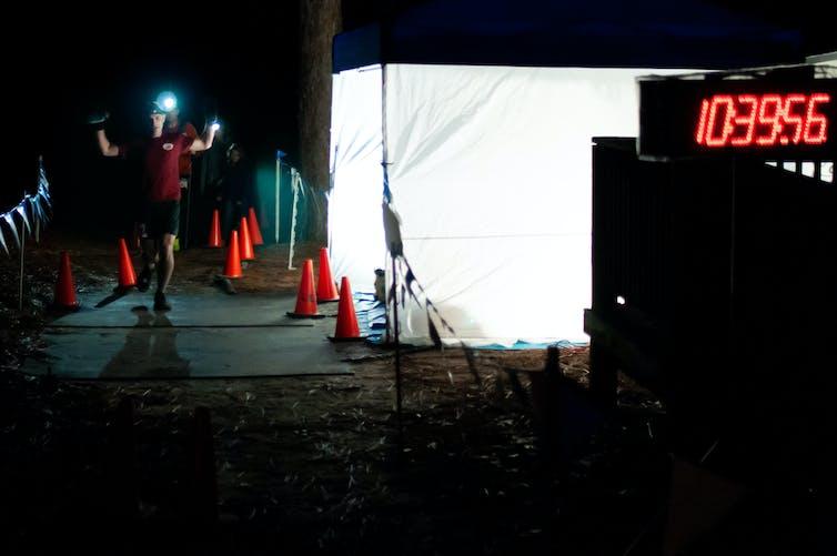 Le vainqueur d'un ultramarathon en Caroline du Nord lève la main alors qu'il franchit la ligne d'arrivée la nuit