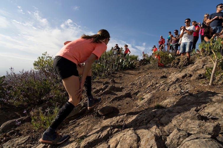 Un coureur escalade une pente rocheuse raide au soleil, lors d'un ultra-marathon en Espagne