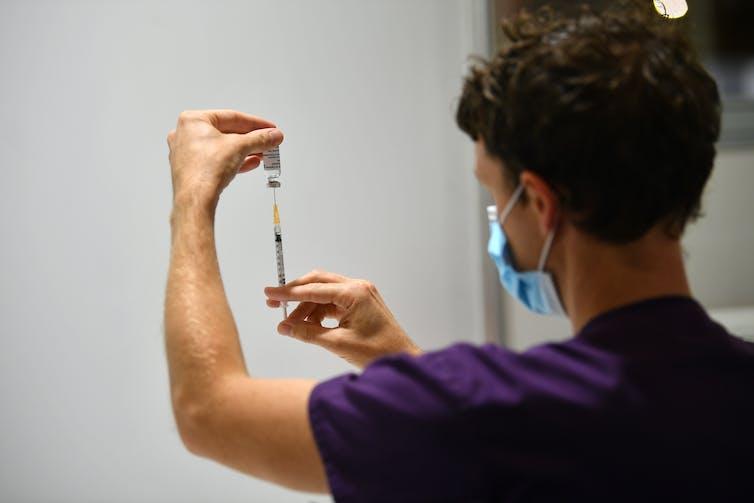 A man prepares a syringe with the AstraZeneca vaccine.