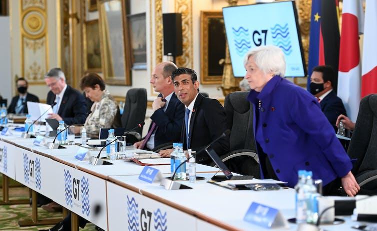 Ministros de Finanzas del G7 sentados en un banco largo con computadoras y micrófonos.