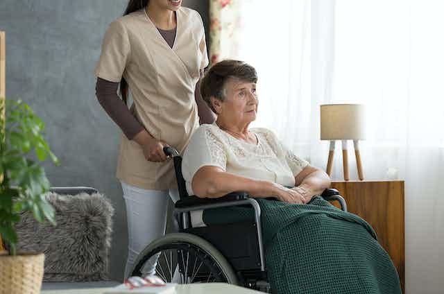 Une femme en fauteuil roulant poussé par une préposée.