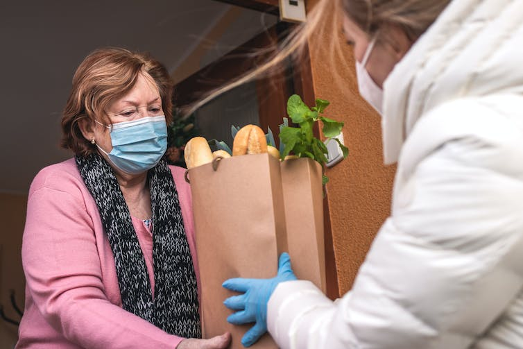 A woman hands a bag of groceries to another woman, both wearing face masks