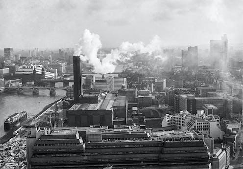 Black and white photo of power station emitting smoke in city skyline