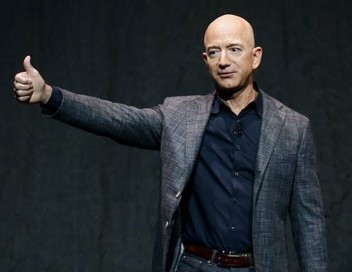 Jeff Bezos wearing gray sport jacket over a navy dress shirt, with no tie, holds his right arm up in the air in a thumbs up position