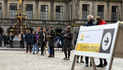 A sign read Hague polling station in English as Dutch people stand in line to vote.