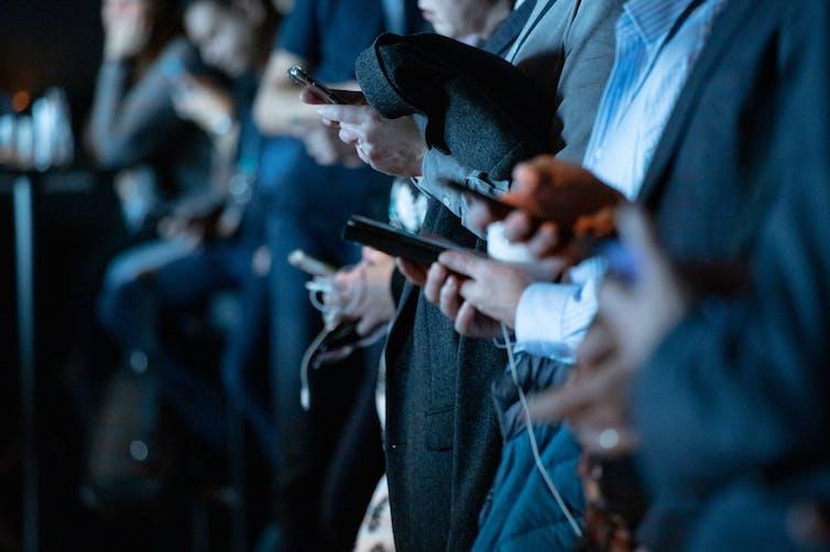 People dressed in suits look at their phones
